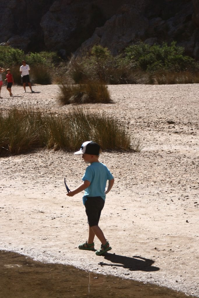 Child walking in the Gorge at Sa Calobra searching for feathers, fish and skipping stones