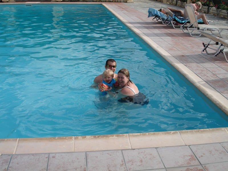 family in the pool at olive garden apartments lassi