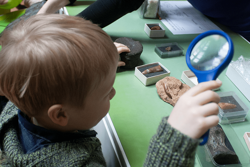 child getting hands-on with the exhibits at the Natural History Museum London