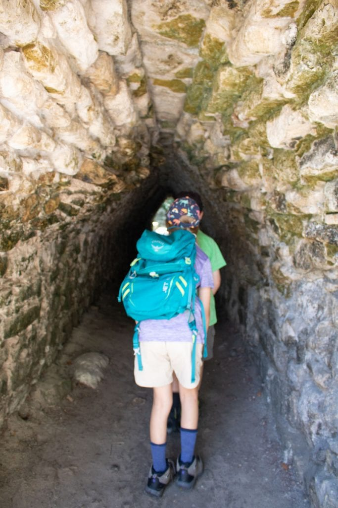 travelled so far kids venturing inside one of the tunnels at Coba