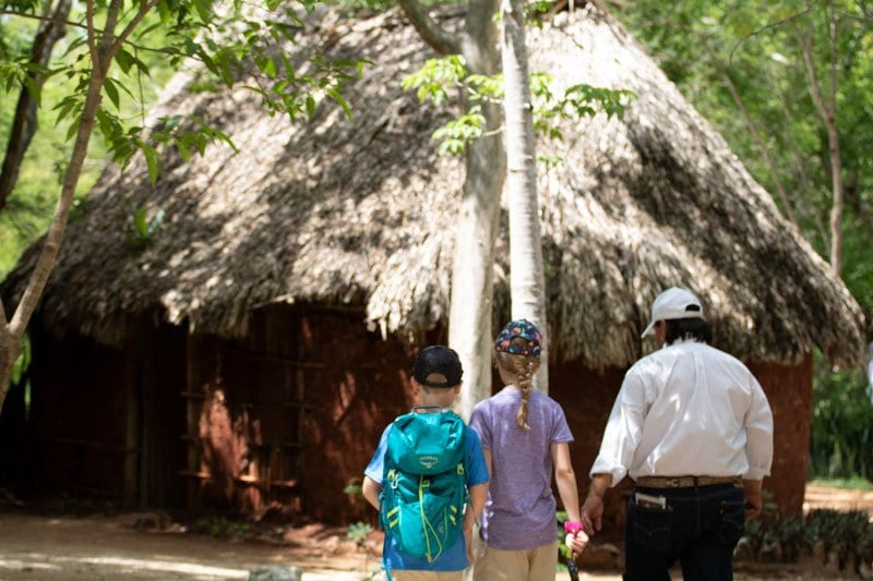 Kids visiting a reconstructed Mayan house in Chichen Itza