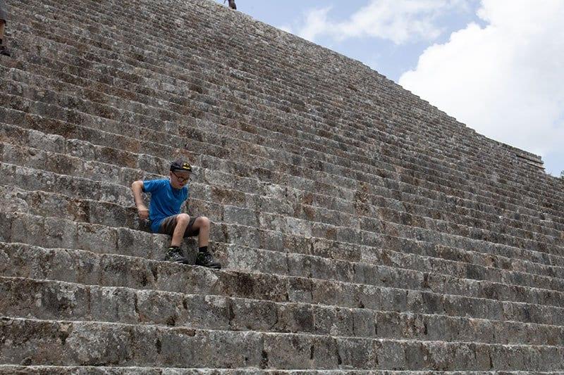 child climbing up the great pyramid at uxmal