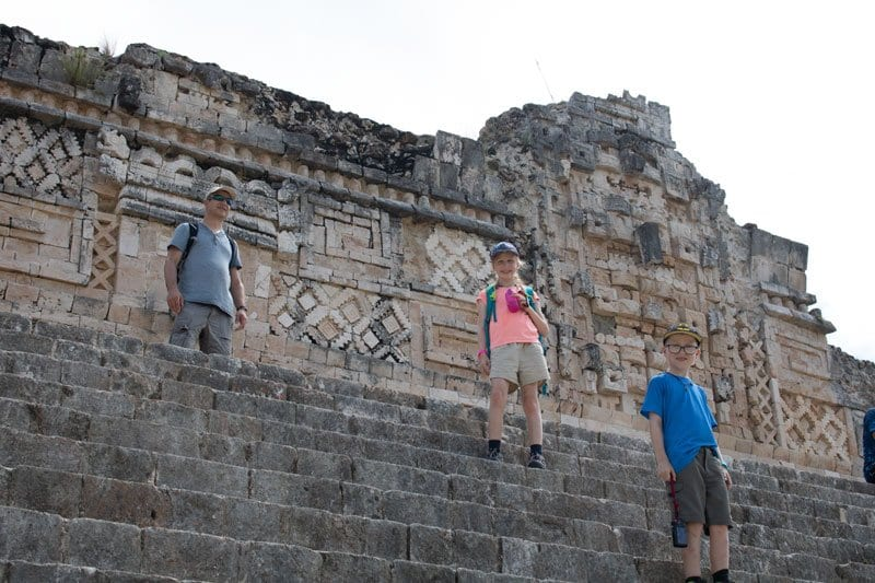 Climbing around the Mayan site at Uxmal family on the steps at the Nunnery Quadrangle